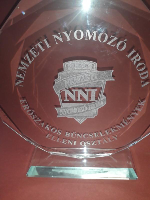 Gravírozott nyolcszögletű csiszolt szélű üvegplakett a Nemzeti Nyomozó  Iroda részére készült. A felirat és a logó lézer gravírozással készült. 7b158c1272